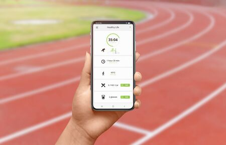 Phone app on running track in woman hand concept. App with daily number of steps and number of calories burned. Banco de Imagens