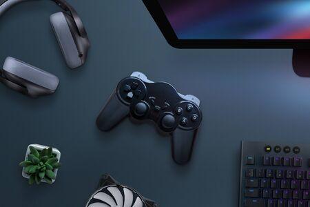 Joypad op bureau omringd met koptelefoon, koeler, toetsenbord en computerscherm. PC-gamingconcept. Bovenaanzicht, plat gelegd.