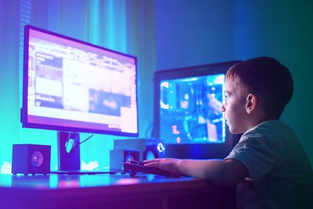 Boy play game on gaming computer or hacking a website concept. Dark scene with lots of RGB lighting.