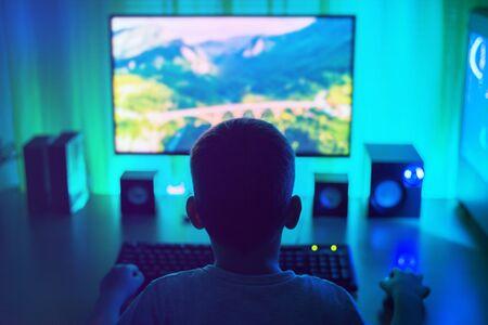 Jongenswerk op de computer. Donkere scène met veel licht. Uitzicht vanaf de achterkant, derde persoon. Concept van een jonge hacker. Stockfoto