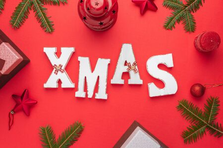 XMAS decorative letters surrounded with Christmas decorations and gifts. Christmas, New Year composition on red surface. Flat lay, top view.