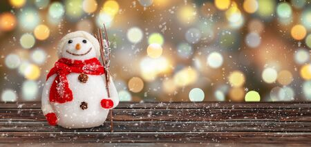 Snowman covered with snowflakes on wooden surface. Christmas background. Copy space.