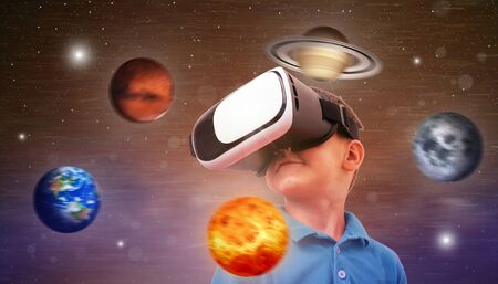 Boy uses a virtual reality headset to study the planets and the universe. Conceptual photo with a boy and planets revolving around his axis.