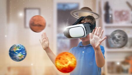 Boy with a virtual reality headset exploring planets in his room. The concept of using modern technologies for education. Stock Photo