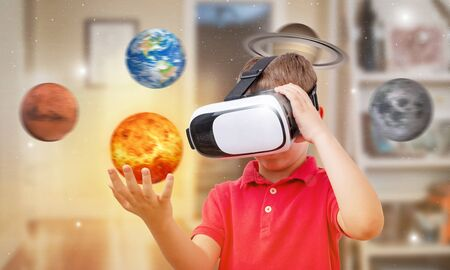 Boy with virtual reality glasses holds the Sun in his room. Concept of using modern technologies for learning.
