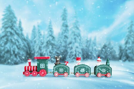 Cute train in the snow. Christmas, New Year background with a lot of snowflakes. Snow trees in background. Stock Photo