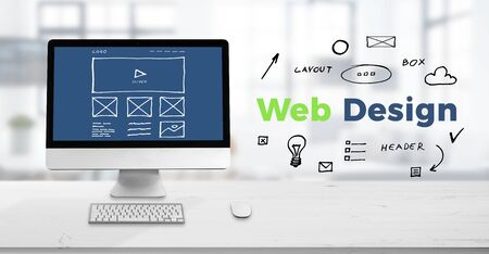 Web design studio concept with computer display on work desk and web design text surrounded with sketch web page elements. Stock Photo