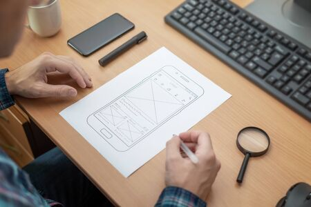 The designer sketches, draws the layout of a mobile phone app on a wireframe. Stock Photo