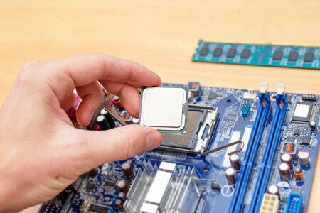 Computer processor installation into motherboard socket. Close-up. Work desk. RAM module beside.