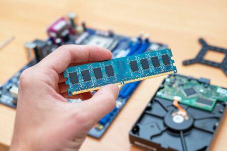 RAM-geheugenmodule in de hand. Moederbord en harde schijf op de achtergrond. Concept van installatie.