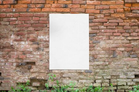 Poster glued to old brick wall. Blank, clean white paper for mockup, design presentation