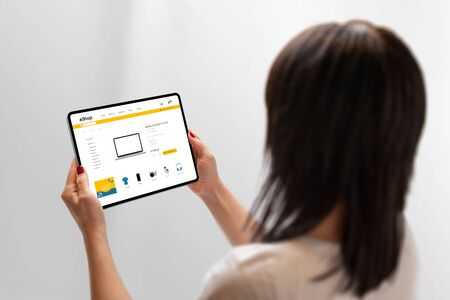 Woman holding tablet and shopping online. Flat design ecommerce web site on tablet display. Concept of buying technology products online