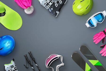 Ski and snowboard equipment placed on the table with copy space in the middle for text, logo or product promotion. Top view, flat lay.