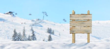 Blank, wooden road sign on snowy mountain, ski resort. Ski lift and slopes in background