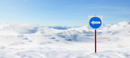 Signpost for skiers stuck in the snow. The arrow shows the left direction of movement. Ski slopes and mountain peaks in background Standard-Bild