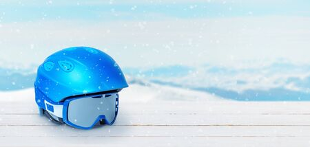 Blue ski helmet and glasses on a white wooden table. Free text space beside. Snowy peaks of mountains in the background