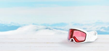 White ski goggles with red glasses on white wooden desk with copy space beside. Mountain peaks in background