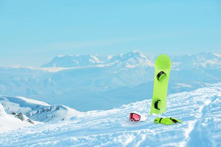 Snowboard equipment laid on the ski slope. Snowy peaks in the background. Copy space beside