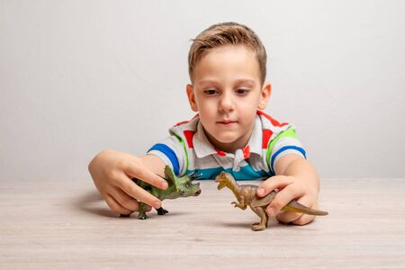 Boy holding dinosaur toys. Concept of developing attention in children through play