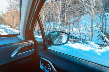 A view of the rearview mirror from inside the car. The concept of driving and traveling in winter
