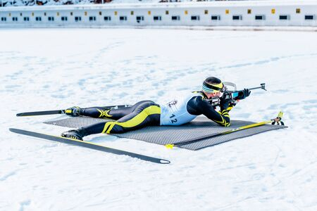 Biathlon lies and shooting target with rifle. Wide angle. Shooting range in the background