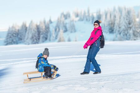Mother dragging the snow sled with boy. Mountain in background. Concept od keep children healthy during the winter Stock Photo