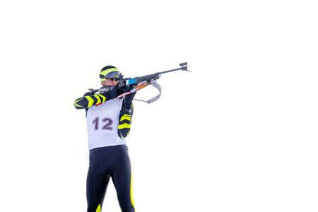Isolated biathlete shoots with rifle in a standing position