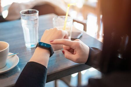 Girl touch smart band, bracelet screen on her arm. Displayed ime and number of steps. Caffee shop in background