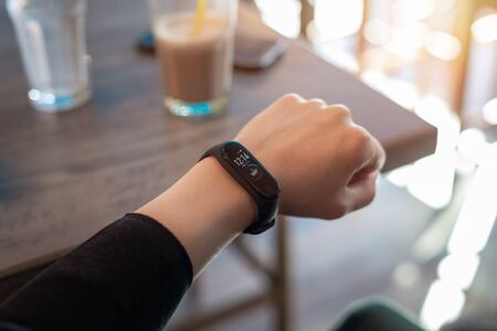 Smart band on woman wrist. Coffee shop in background