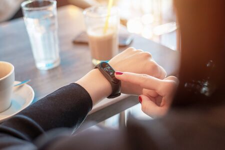 Bracelet activity tracker on woman wrist. Woman touch smart band screen with time and number of steps Stok Fotoğraf