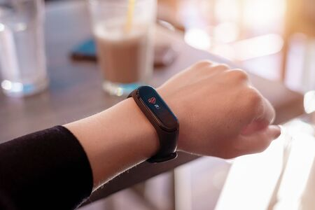 Girl measures her heart rate with a smart bracelet. Close-up. Coffee shop in background