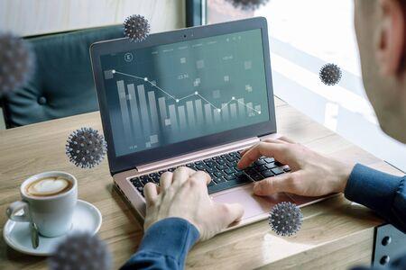Impact of coronavirus on stock markets concept on laptop computer. Coronaviruses surround a man with laptop Foto de archivo