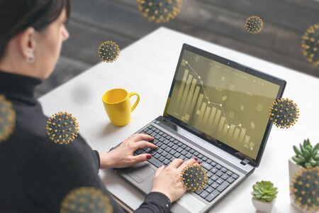 Woman analyzes the values of stocks in a market on laptop computer surrounded by corona viruses concept