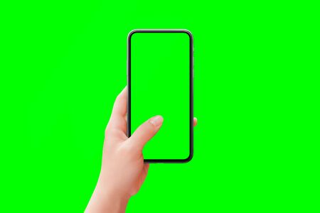 Phone mockup in woman hand isolated in chroma key green. Front position. Modern phone with round edges