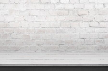 Clean desk for product promotion. White brick wall in background Stok Fotoğraf