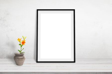 Picture frame mockup on white wooden desk leaning against a wall. Plant and pot beside