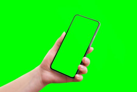 Phone mockup isolated in chroma key green. Soft retouched woman hand holds the phone. Close-up