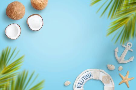 Summer travel conposition on blue surface with coconuts, palm leaves, shells, starfish, lifebelt, anchor