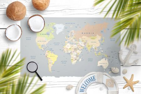 World map on a white wooden table surrounded with coconut, palm leaves, shells, starfish, lifebelt, anchor, magnifier. Concept of travel and finding tropical destinations