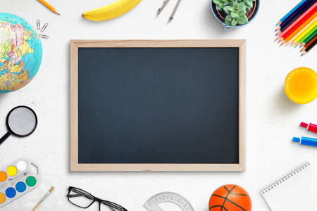 School chalkboard mockup on work desk. Composition of a student's desk with stationery items, toys, snack. Empty board for promo text