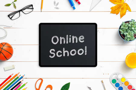 Online school on tablet surrounded by school supplies on white wooden desk. Top view, flat lay composition. Classes at the time of virus epidemic concept