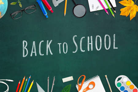 Back to school text written in chalk on a board, surrounded by school supplies