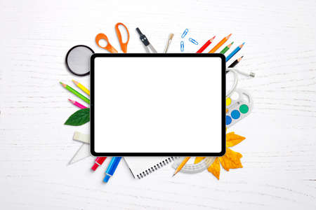 Tablet with isolated screen for mockup, app or website presentation surrounded by school supplies Stok Fotoğraf