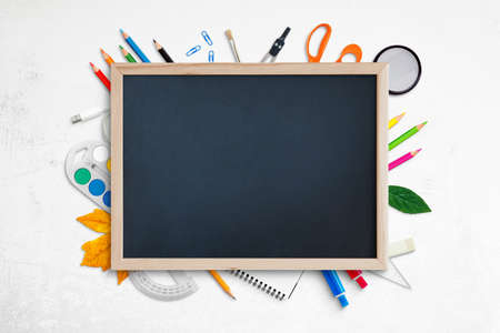 Empty chalkboard for promo text surrounded by school supplies on white desk. Top view, flat lay, composition