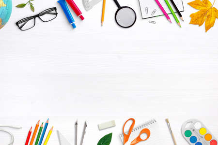 School supplies on white desk with free space for promo text in the middle. School equipment composition. Top view, flat lay