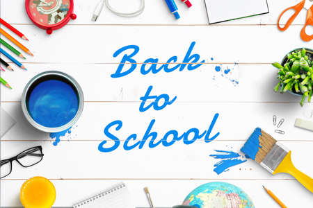 Back to School text painted with brush on white wooden desk. Top view composition with school supplies