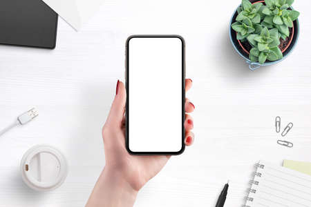 Phone mockup in woman hand. Top view, flat lay. Coffee, pad, plant, pen, usb cable beside Stok Fotoğraf