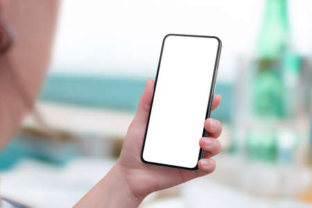 Mobile phone mockup in woman hand. View above shoulder. Modern smart phone with round edges