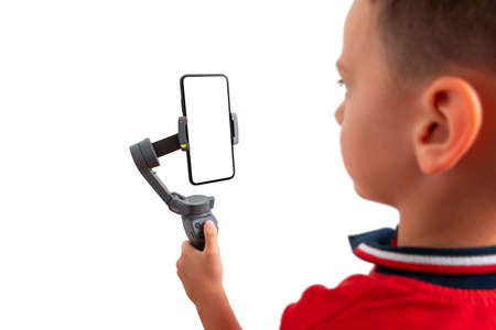 Boy holding gimbal with smart phone in vertical position. Isoalted background and display for mockup. Concept of shooting and photography with a mobile phone Stok Fotoğraf
