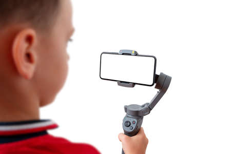 Boy is recording with a mobile phone on the gimbal. Isolated background and phone display for mockup